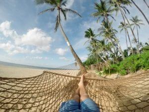 The feet of someone relaxing in a hammock on a beach